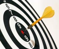 Target and dart. A dart sticks in the center of a target, a perfect bullseye Stock Photos