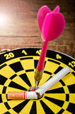 Target dart and arrow with tobacco. Stock Image