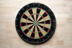 Target dart board on the wooden table background. Center point, head to target marketing and business concept Stock Photos