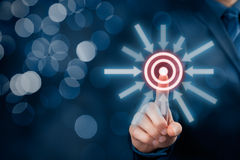 Target goal trigger. Marketing targeting, goal and trigger concepts. Businessman click on virtual target, bokeh in background royalty free stock photo