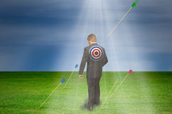 Target market bullseye marketing success. Target market concept showing a man with a target on his back with arrows all around him as a flying arrow is heading Stock Photography