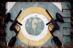 Target and paintball markers. Two paintball markers and yellow target on wooden board Stock Photography