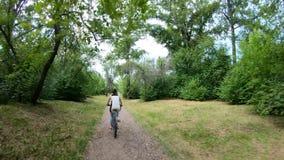 target114_1_ park Dziewczyna jedzie rower na lasowym śladzie swobodny ruch zdjęcie wideo