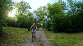target114_1_ park Dziewczyna jedzie rower na lasowym śladzie swobodny ruch zbiory wideo