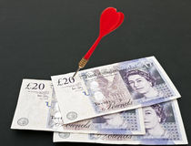 Target pounds sterling - business financial. Red dart in pound notes - money market metaphor stock photography