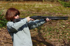 Target practice. A white female taking taget practice with a 12 gauge shotgun Stock Image