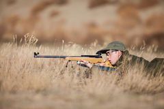 Target Shoot. A young army cadet laying in the dry grass target shooting Royalty Free Stock Image