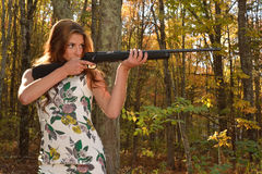 Target shooting. Young lady with a rifle surrounded by autumn woods in a shooting stance Royalty Free Stock Photography
