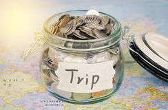 Target for travel - concept saving money in a glass and word `trip` on map. Stock Photo