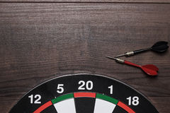 Target and two darts on brown wooden table Royalty Free Stock Photo