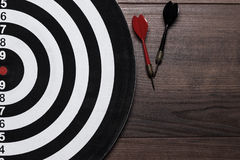 Target and two darts on wooden background Royalty Free Stock Photos