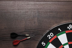 Target and two darts on wooden table Royalty Free Stock Image