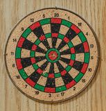 Target on a wood background. Colorful wooden dartboard and a metal perimeter with a wooden background stock images