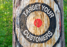 Target your customers. Written in white block text inside bulls eye target painted on a tree Royalty Free Stock Images