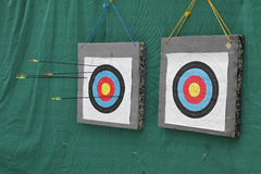 Targets. Two archery targets on green background. One with a couple of arrows, second is empty Royalty Free Stock Images