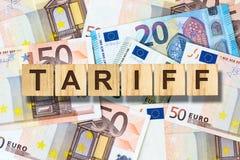 Tariff inskrift på träkvarteren på bakgrunden av eurosedlarna Aff?r finans fotografering för bildbyråer