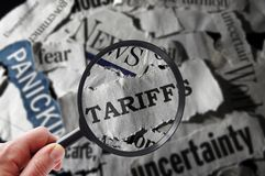 Tariff news headlines look. Magnifying glass with tariff related newspaper headlines royalty free stock photos