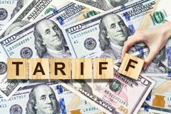 Tariffen den kvinnliga handen - gjorde upp inskriften på träkvarter på bakgrunden av dollarsedlarna Aff?r finans royaltyfri foto
