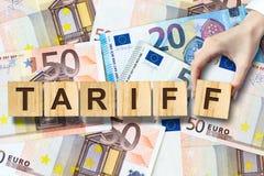 Tariffen den kvinnliga handen - gjorde upp inskriften på träkvarter på bakgrunden av eurosedlar Aff?r finans royaltyfria bilder