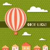 Tarjeta abstracta de la buena suerte con el globo del aire caliente, las nubes, las casas y el fondo del modelo de tres tréboles  Foto de archivo