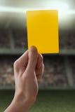 Tarjeta amarilla con la mano del árbitro que da un penalt Foto de archivo libre de regalías