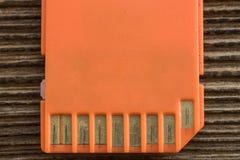 Tarjeta anaranjada del SD de la memoria, viejo fondo de madera Fotos de archivo