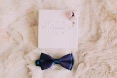 Tarjeta azul de la invitación de la corbata de lazo y de la boda con las rosas rosadas minúsculas en el fondo blanco de la piel Fotografía de archivo libre de regalías