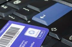 Tarjeta azul global de la compañía exenta de impuestos en el teclado negro del cuaderno Fotos de archivo libres de regalías