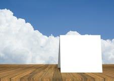tarjeta blanca en la tabla de madera vacía y cielo azul y nube hermosos en fondo plantilla de la exhibición del producto Presenta Imagenes de archivo