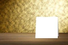 Tarjeta blanca puesta en el escritorio de madera o el piso de madera en fondo abstracto borroso de la textura de la pared del oro Fotos de archivo libres de regalías