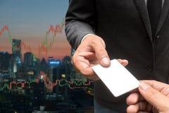 Tarjeta comercial del crédito en blanco del control del hombre de negocios y divisas que negocian a Lin Foto de archivo