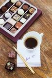Tarjeta con amor del mensaje usted, taza de café y caramelos de chocolate Imágenes de archivo libres de regalías