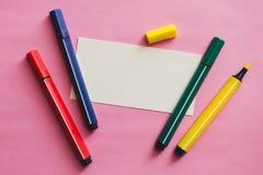 Tarjeta con el espacio de la copia y marcadores coloreados en un fondo rosado foto de archivo libre de regalías