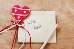 Tarjeta con el mensaje con amor en la letra y el corazón rojo de madera o foto de archivo