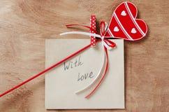 Tarjeta con el mensaje con amor en la letra y el corazón rojo de madera o fotografía de archivo