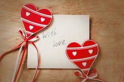 Tarjeta con el mensaje con amor en la letra y los corazones rojos de madera imágenes de archivo libres de regalías
