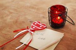 Tarjeta con el mensaje con el amor en la letra, vela romántica Holde fotos de archivo