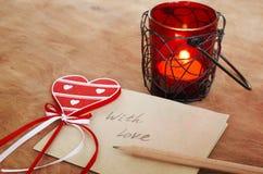 Tarjeta con el mensaje con el amor en la letra, vela romántica Holde fotos de archivo libres de regalías
