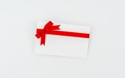 Tarjeta con los arqueamientos rojos de las cintas Fotos de archivo libres de regalías