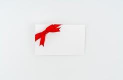 Tarjeta con los arqueamientos rojos de las cintas Fotos de archivo