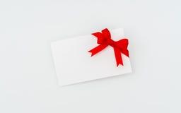 Tarjeta con los arqueamientos rojos de las cintas Foto de archivo libre de regalías