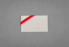 Tarjeta con los arqueamientos rojos de las cintas Fotografía de archivo libre de regalías