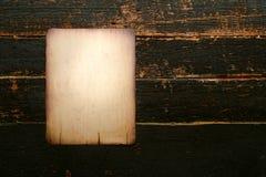 Tarjeta de aviso de papel antigua en la pared vieja de madera de Grunge Imagen de archivo libre de regalías