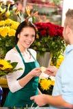 Tarjeta de compra sonriente de las flores del cliente del hombre del florista Imágenes de archivo libres de regalías