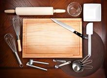 Tarjeta de corte con otras herramientas de cocinar Fotos de archivo libres de regalías