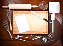 Tarjeta de corte con otras herramientas de cocinar Imágenes de archivo libres de regalías