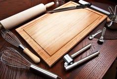 Tarjeta de corte con otras herramientas de cocinar Foto de archivo