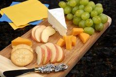 Tarjeta de corte con queso y fruta Imagenes de archivo