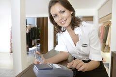 Tarjeta de crédito arrebatadora acompañante del departamento en el contador de la tienda Fotos de archivo