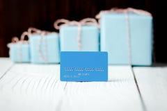 Tarjeta de crédito azul de la composición del Año Nuevo de la Navidad con los regalos en vagos Imagenes de archivo